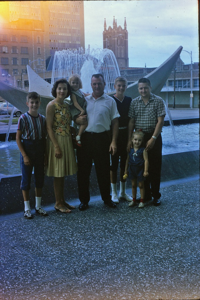 This picture was taken in the mid-sixties after my uncle and his family moved to Houston.  From left, my cousin, David, Aunt Marlene, Uncle Bud holding my cousin, Mary, my cousin, Buddy, and my dad.  The four year old standing in front of my dad is me.  And my mom took the picture.
