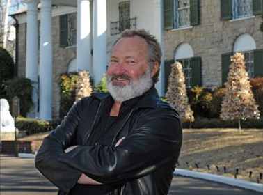 "Randy Quaid, aka ""Cousin Eddie"" from Christmas Vacation fame, sitting in front of the Graceland mansion."