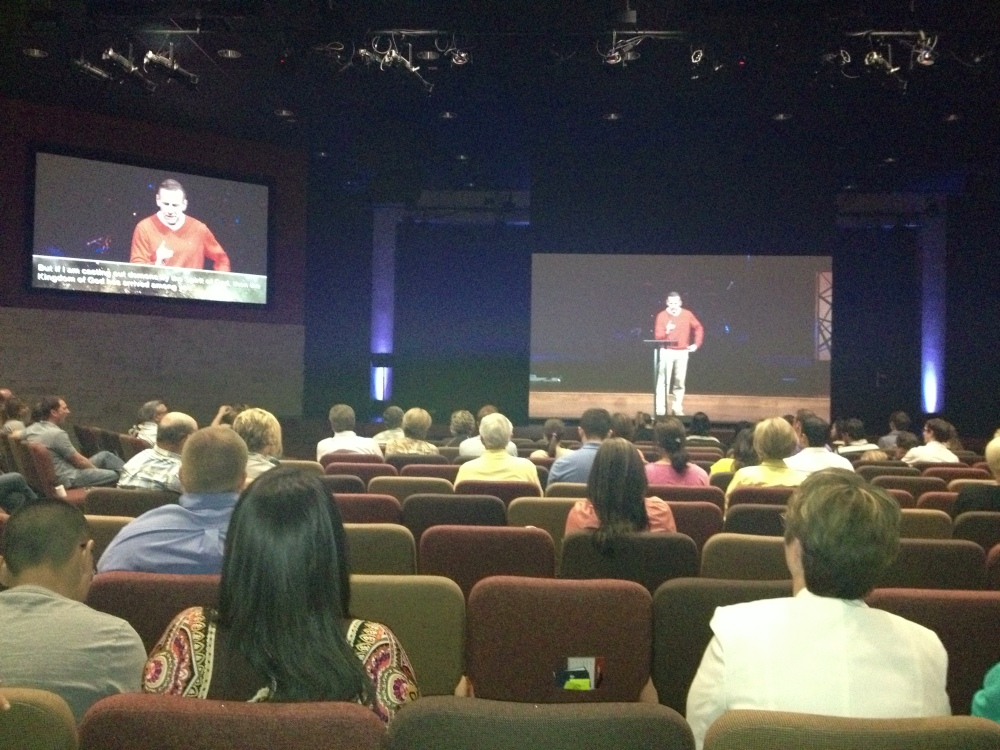 Rick Atchley preaching via satellite from The Hills, on the big screen at the west Fort Worth branch